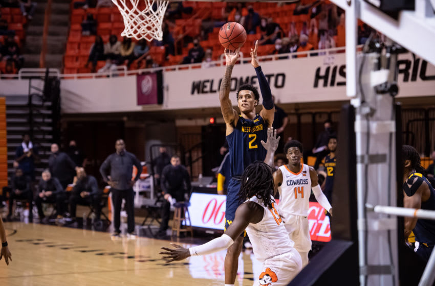 Jan 4, 2021; Stillwater, Oklahoma, USA; West Virginia Mountaineers forward Jalen Bridges (2) shoots the ball over Oklahoma State Cowboys guard Isaac Likekele (13) during the first half at Gallagher-Iba Arena. Mandatory Credit: Rob Ferguson-USA TODAY Sports