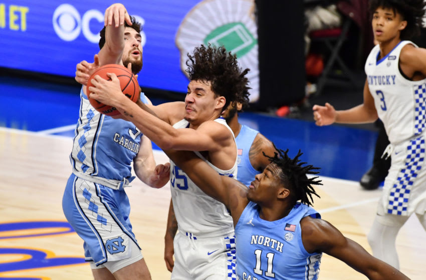 Dec 19, 2020; Cleveland, Ohio, USA; Kentucky Wildcats forward Lance Ware (55) fights for a rebound with North Carolina Tar Heels guard Andrew Platek (3) and forward Day'Ron Sharpe (11) during the second half at Rocket Mortgage FieldHouse. Mandatory Credit: Ken Blaze-USA TODAY Sports