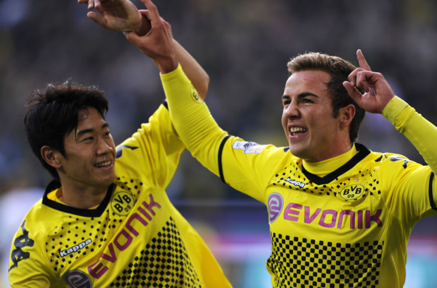 Dortmund's midfielder Mario Goetze (R) celebrates scoring with Dortmund's Japanese forward Shinji Kagawa during the German first division Bundesliga football match Borussia Dortmund vs VfL Wolfsburg in the western German city of Dortmund on November 5, 2011. AFP PHOTO / PATRIK STOLLARZ +++ RESTRICTIONS / EMBARGO - DFL LIMITS THE USE OF IMAGES ON THE INTERNET TO 15 PICTURES (NO VIDEO-LIKE SEQUENCES) DURING THE MATCH AND PROHIBITS MOBILE (MMS) USE DURING AND FOR FURTHER TWO HOURS AFTER THE MATCH. FOR MORE INFORMATION CONTACT DFL. (Photo credit should read PATRIK STOLLARZ/AFP/Getty Images)