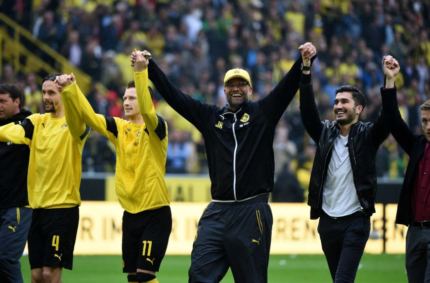Dortmund's head coach Juergen Klopp (C) and Dortmund's players celebrate after the German first division Bundesliga football match between Borussia Dortmund and SV Werder Bremen at the Signal Iduna Park in Dortmund, western Germany on May 23, 2015. Dortmund won the match 3-2. AFP PHOTO / PATRIK STOLLARZ RESTRICTIONS - DFL RULES TO LIMIT THE ONLINE USAGE DURING MATCH TIME TO 15 PICTURES PER MATCH. IMAGE SEQUENCES TO SIMULATE VIDEO IS NOT ALLOWED AT ANY TIME. FOR FURTHER QUERIES PLEASE CONTACT DFL DIRECTLY AT + 49 69 650050. (Photo credit should read PATRIK STOLLARZ/AFP via Getty Images)