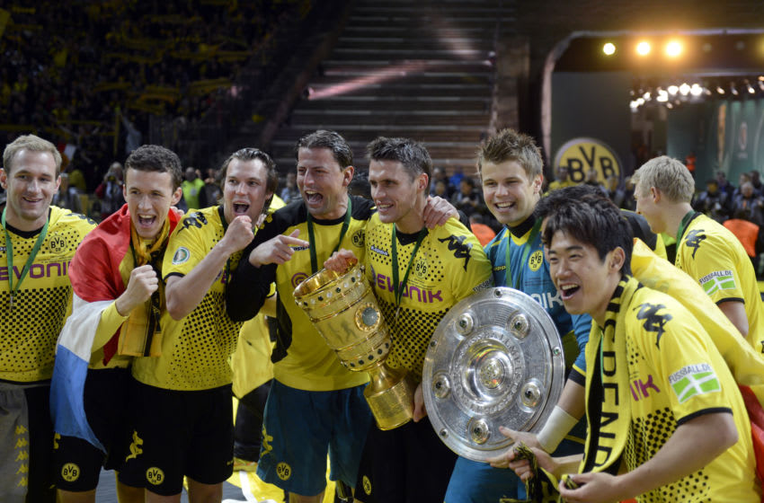 Dortmund's players celebrate with the trophies of the German Cup (C) and the Bundesliga first division (R) after their team won the German cup
