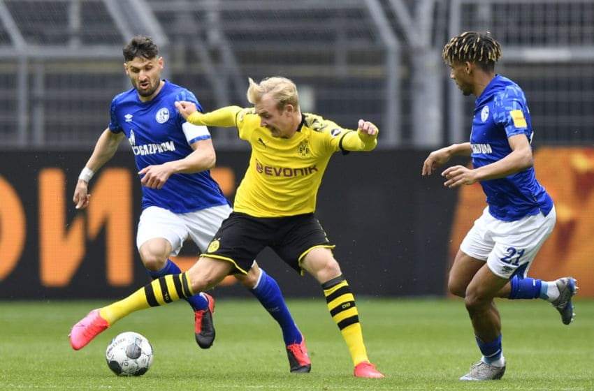 Dortmund's German forward Julian Brandt vies for the ball with Schalke's German midfielder Daniel Caligiuri (L) and Schalke's French defender Jean-Clair Todibo during the German first division Bundesliga football match BVB Borussia Dortmund v Schalke 04 on May 16, 2020 in Dortmund, western Germany as the season resumed following a two-month absence due to the novel coronavirus COVID-19 pandemic. (Photo by Martin Meissner / POOL / AFP) / DFL REGULATIONS PROHIBIT ANY USE OF PHOTOGRAPHS AS IMAGE SEQUENCES AND/OR QUASI-VIDEO (Photo by MARTIN MEISSNER/POOL/AFP via Getty Images)