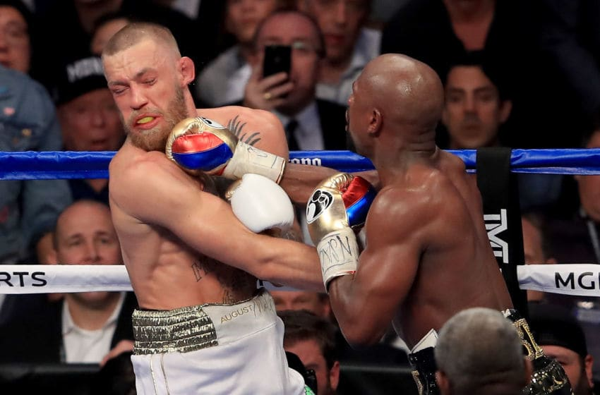 LAS VEGAS, NV - AUGUST 26: (R-L) Floyd Mayweather Jr. throws a punch at Conor McGregor during their super welterweight boxing match on August 26, 2017 at T-Mobile Arena in Las Vegas, Nevada. (Photo by Sean M. Haffey/Getty Images)