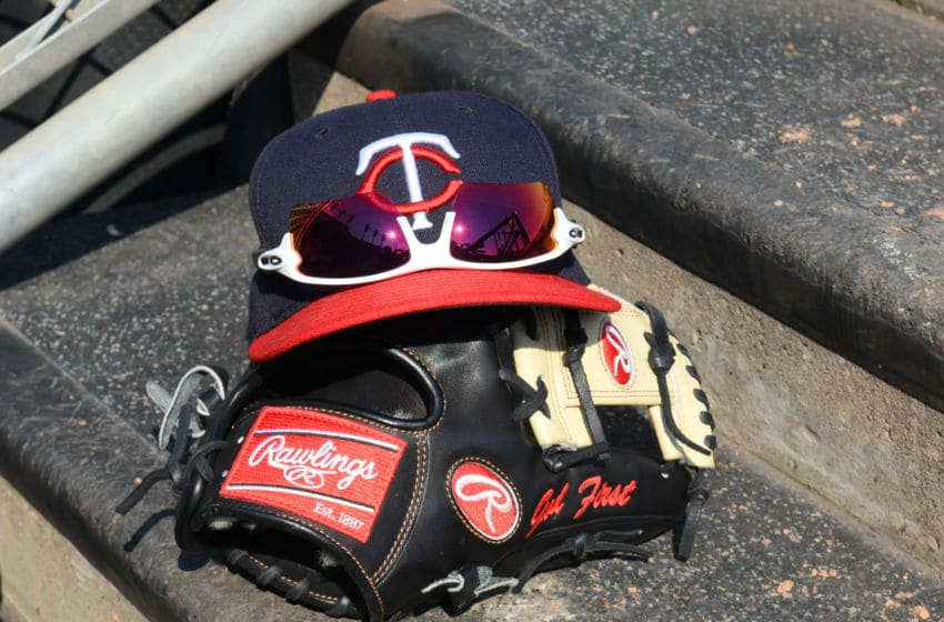 DETROIT, MI - SEPTEMBER 19: A detailed view of a Minnesota Twins baseball hat and a Rawlings glove sitting on the dugout steps during the game against the Detroit Tigers at Comerica Park on September 19, 2018 in Detroit, Michigan. The Twins defeated the Tigers 8-2. (Photo by Mark Cunningham/MLB Photos via Getty Images)