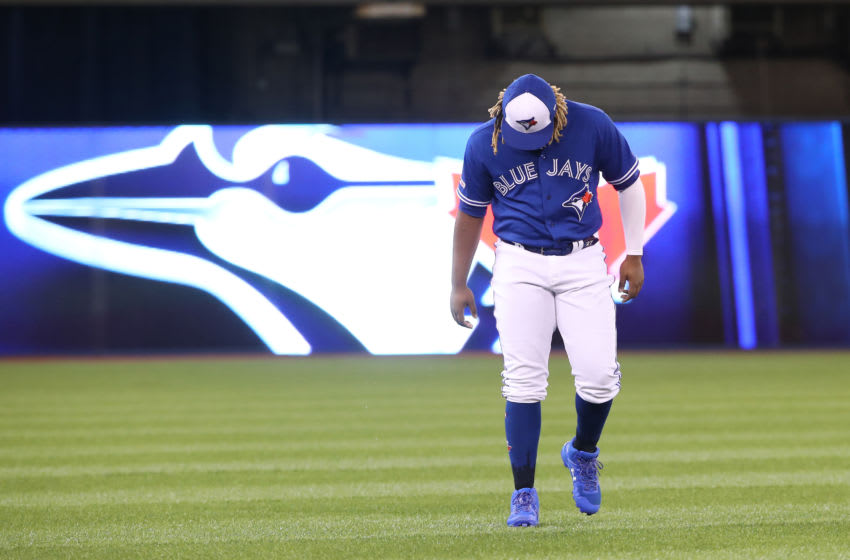 TORONTO, ON - MAY 10: Vladimir Guerrero Jr. #27 of the Toronto Blue Jays warms up in the outfield as the team logo is displayed behind him on an auxiliary scoreboard before the start of MLB game action against the Chicago White Sox at Rogers Centre on May 10, 2019 in Toronto, Canada. (Photo by Tom Szczerbowski/Getty Images)