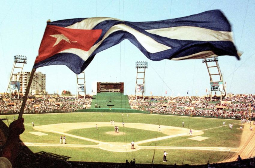 A Cuban fan waves the Cuban flag during the historic baseball game between the Baltimore Orioles and the Cuban national team at LatinoAmericano Stadium in Havana, Cuba 28 March, 1999. The Baltimore Orioles won the contest in 3-2 in eleven innings. AFP PHOTO/Adalberto ROQUE (Photo by Adalberto ROQUE / AFP) (Photo by ADALBERTO ROQUE/AFP via Getty Images)