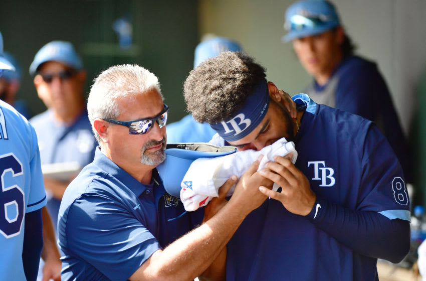 SARASOTA, FLORIDA - MARCH 02: Trainer Mike Sandoval of the Tampa Bay Rays assists prospect Garrett Whitley #8 who was hit by a foul ball off the bat of Renato Nunez of the Baltimore Orioles during the fourth inning of a Grapefruit League spring training game at Ed Smith Stadium on March 02, 2020 in Sarasota, Florida. (Photo by Julio Aguilar/Getty Images)