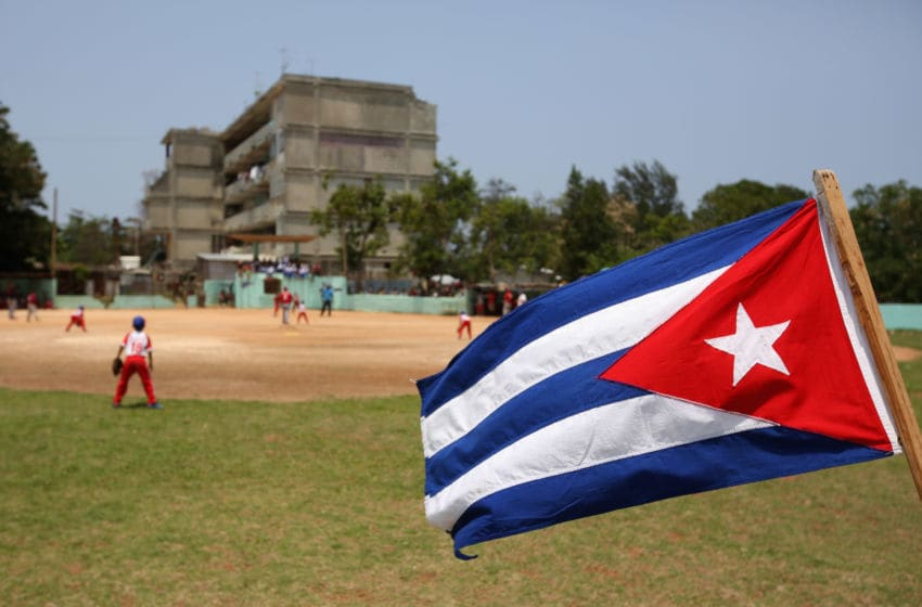 HAVANA, CUBA - MAY 09: The Cuban flag flies in the outfield as kids play baseball on May 09, 2015 in the Alamar subarb of Havana, Cuba. (Photo by Ezra Shaw/Getty Images)