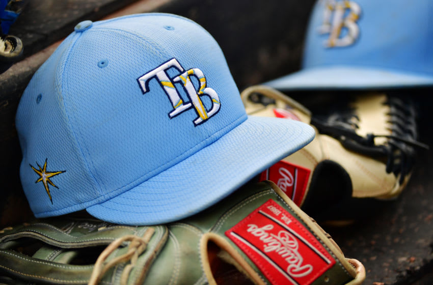 SARASOTA, FLORIDA - MARCH 02: A Tampa Bay Rays hat sits on top of a glove in the dugout during a Grapefruit League spring training game between the Baltimore Orioles and the Tampa Bay Rays at Ed Smith Stadium on March 02, 2020 in Sarasota, Florida. (Photo by Julio Aguilar/Getty Images)