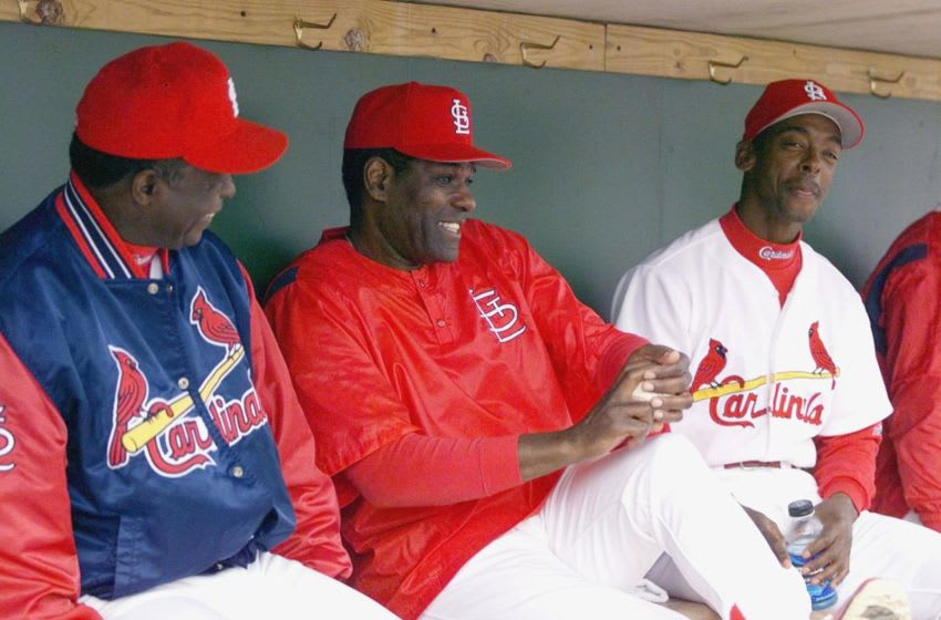 St. Louis Cardinals legends Lou Brock (L) and Bob Gibson (C) joke with Willie McGee in the dugout prior to the start of their spring training game 15 March 1999, against the Atlanta Braves at Rodger Dean Stadium in Jupiter, Florida. (ELECTRONIC IMAGE) AFP PHOTO/Robert SULLIVAN (Photo by ROBERT SULLIVAN / AFP) (Photo credit should read ROBERT SULLIVAN/AFP via Getty Images)