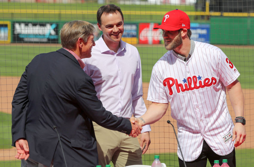 CLEARWATER, FL - MARCH 2: John Middleton, Philadelphia Phillies managing parter, shakes hands with Bryce Harper as general manager Matt Klentak looks on during the press conference introducing Harper as a member of the Philadelphia Phillies on Saturday March 2, 2019 at Spectrum Field in Clearwater, Florida. (Photo by Mike Carlson/MLB via Getty Images)