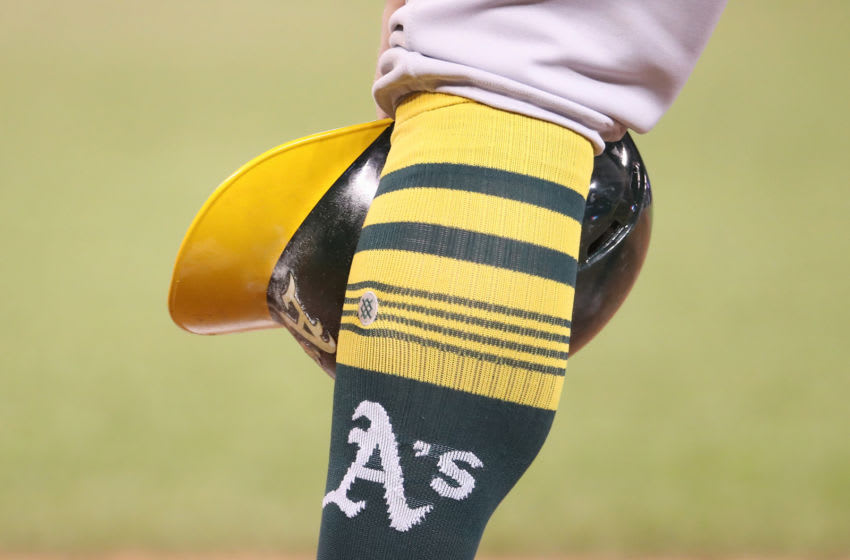 TORONTO, ON - APRIL 28: Robbie Grossman #8 of the Oakland Athletics waits during a pitching change as he rests his helmet beside his sock showing the team logo in the eleventh inning during MLB game action against the Toronto Blue Jays at Rogers Centre on April 28, 2019 in Toronto, Canada. (Photo by Tom Szczerbowski/Getty Images)