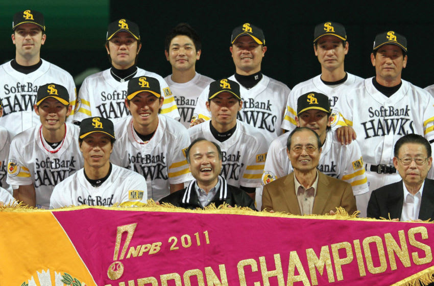 In a picture taken on November 20, 2011, Pacific League champions Softbank Hawks (first row L-R) manager Koji Akiyama, owner Masayoshi Son and chairman Sadaharu Oh smile with their players as they hold a large pennant to celebrate victory of the Japan Series professional baseball championship in Fukuoka, western Japan. The Hawks defeated Central League champion Chunichi Dragons 3-0 and clinched the Japan Series title 4-3. AFP PHOTO / JIJI PRESS (Photo by JIJI PRESS / JIJI PRESS / AFP) / Japan OUT (Photo credit should read JIJI PRESS/AFP via Getty Images)