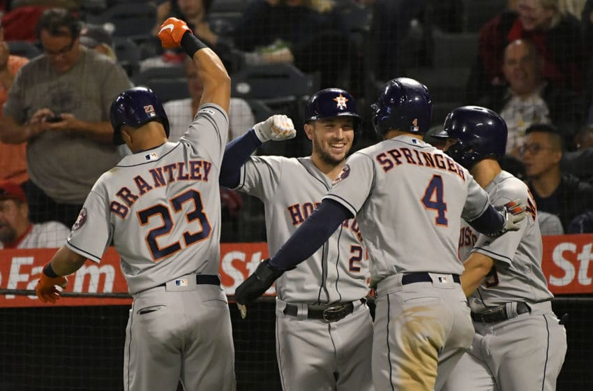 ANAHEIM, CA - SEPTEMBER 27: Michael Brantley #23 of the Houston Astros celebrates with team mates Alex Bregman #2, George Springer #4 and Jose Altuve #27 after hitting a three run home run against pitcher Luis Garcia #40 of the Los Angeles Angels in the eighth inning at Angel Stadium of Anaheim on September 27, 2019 in Anaheim, California. (Photo by John McCoy/Getty Images)