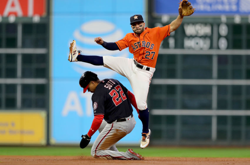 HOUSTON, TEXAS - OCTOBER 30: Jose Altuve #27 of the Houston Astros turns the double play against Juan Soto #22 of the Washington Nationals during the second inning in Game Seven of the 2019 World Series at Minute Maid Park on October 30, 2019 in Houston, Texas. (Photo by Elsa/Getty Images)