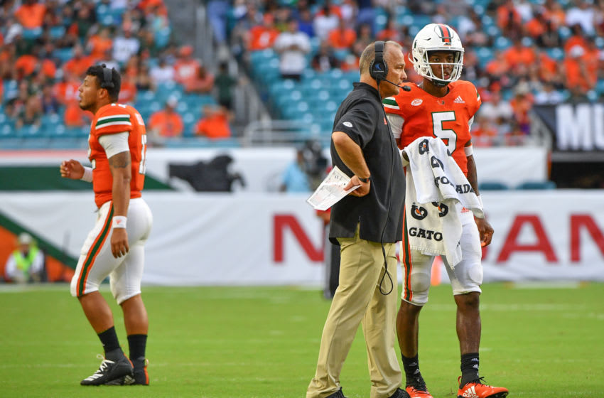 MIAMI, FL - SEPTEMBER 22: Malik Rosier #12 walks to the sidelines as head coach Mark Richt speaks with N'Kosi Perry #5 of the Miami Hurricanes in the fourth quarter against the Florida International Golden Panthers at Hard Rock Stadium on September 22, 2018 in Miami, Florida. (Photo by Mark Brown/Getty Images)