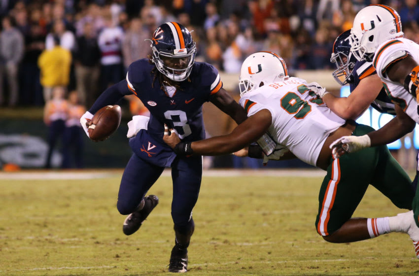 CHARLOTTESVILLE, VA - OCTOBER 13: Pat Bethel #93 of the Miami Hurricanes dives at Bryce Perkins #3 of the Virginia Cavaliers in the first half during a game at Scott Stadium on October 13, 2018 in Charlottesville, Virginia. (Photo by Ryan M. Kelly/Getty Images)