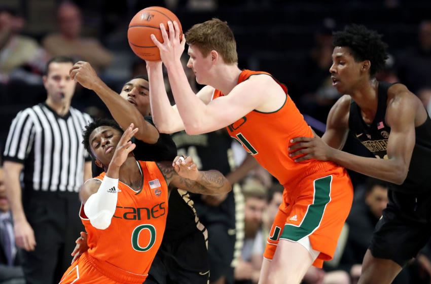 WINSTON-SALEM, NORTH CAROLINA - FEBRUARY 26: Sam Waardenburg #21 tries to get the ball to teammate Chris Lykes #0 of the Miami (Fl) Hurricanes as Brandon Childress #0 of the Wake Forest Demon Deacons tries to stop him during their game at LJVM Coliseum Complex on February 26, 2019 in Winston-Salem, North Carolina. (Photo by Streeter Lecka/Getty Images)