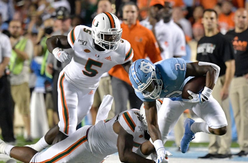 CHAPEL HILL, NORTH CAROLINA - SEPTEMBER 07: Amari Carter #5 and Andrew Barnes #36 of the Miami Hurricanes tackle Dyami Brown #2 of the North Carolina Tar Heels during the first half of their game at Kenan Stadium on September 07, 2019 in Chapel Hill, North Carolina. (Photo by Grant Halverson/Getty Images)