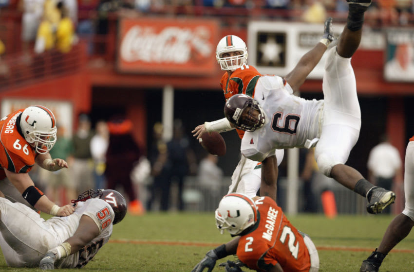 MIAMI - DECEMBER 7: Quarterback Ken Dorsey #11 of the University of Miami Hurricanes drops back to pass while linebacker Vegas Robinson #6 of the Virginia Polytechnic Institute and State University Hokies takes a tumble during the game at the Orange Bowl on December 7, 2002 in Miami, Florida. The Hurricanes won 56-45. (Photo by Jed Jacobsohn/Getty Images)