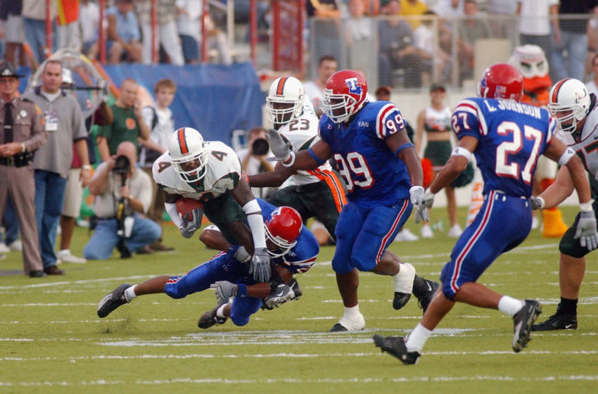 SHREVEPORT, LA - AUGUST 28: Wide receiver Devin Hester #4 of the University of Miami Hurricanes is tackled by free safety Michael Johnson #21 of the Louisiana Tech University Bulldogs during the game at Independence Stadium on August 28, 2003 in Shreveport, Louisiana. Miami defeated Louisiana Tech 48-9. (Photo by Chris Graythen/Getty Images)