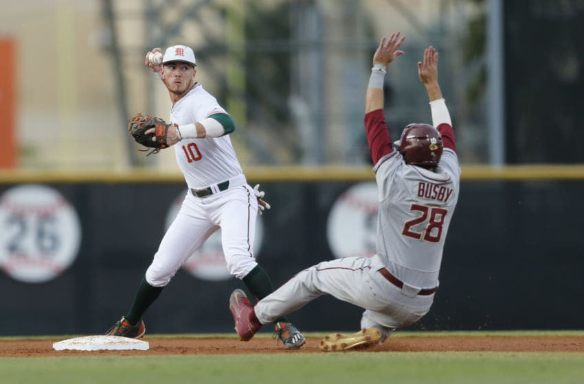 CORAL GABLES, FL - April 21: Romy Gonzalez #10 of the Miami Hurricanes turns the double play getting Dylan Busby #28 of the Florida State Seminoles out at second base during first inning action on April 21, 2017 at Alex Rodriguez Park at Mark Light Field in Coral Gables, Florida. The Seminoles defeated the Hurricanes 6-3. (Photo by Joel Auerbach/Getty Images)