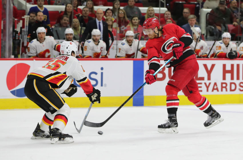 RALEIGH, NC - FEBRUARY 03: Carolina Hurricanes defenseman Dougie Hamilton (19) shoots the puck while Calgary Flames defenseman Noah Hanifin (55) tires to block him during the 1st period of the Carolina Hurricanes game versus the Calgary Flames on February 3rd, 2019 at PNC Arena in Raleigh, NC. (Photo by Jaylynn Nash/Icon Sportswire via Getty Images)