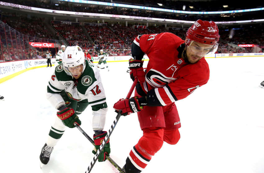 RALEIGH, NC - MARCH 23: Nino Niederreiter #21 of the Carolina Hurricanes battles for a loose puck in the corner of the ice with Eric Staal #12 of the Minnesota Wild during an NHL game on March 23, 2019 at PNC Arena in Raleigh, North Carolina. (Photo by Gregg Forwerck/NHLI via Getty Images)