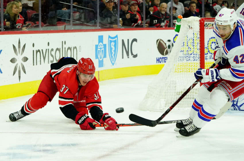 RALEIGH, NC - NOVEMBER 7: Andrei Svechnikov #37 of the Carolina Hurricanes and Brendan Smith #42 of the New York Rangers battle for the loose puck during an NHL game on November 7, 2019 at PNC Arena in Raleigh, North Carolina. (Photo by Gregg Forwerck/NHLI via Getty Images)