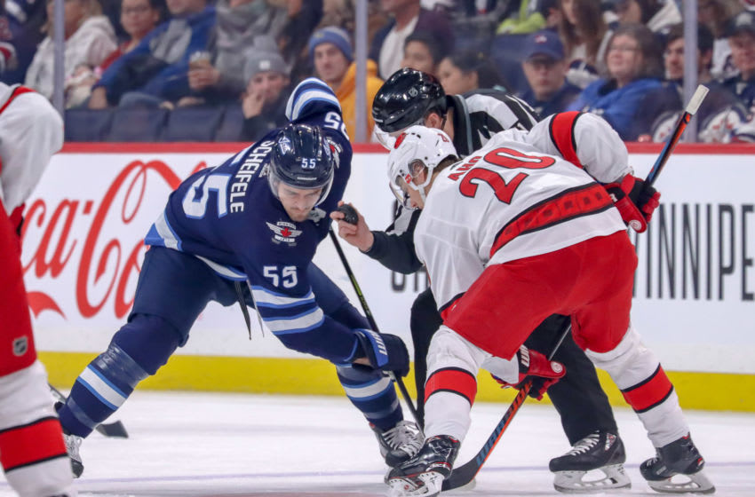 WINNIPEG, MB - DECEMBER 17: Mark Scheifele #55 of the Winnipeg Jets takes a first period face-off against Sebastian Aho #20 of the Carolina Hurricanes at the Bell MTS Place on December 17, 2019 in Winnipeg, Manitoba, Canada. (Photo by Darcy Finley/NHLI via Getty Images)