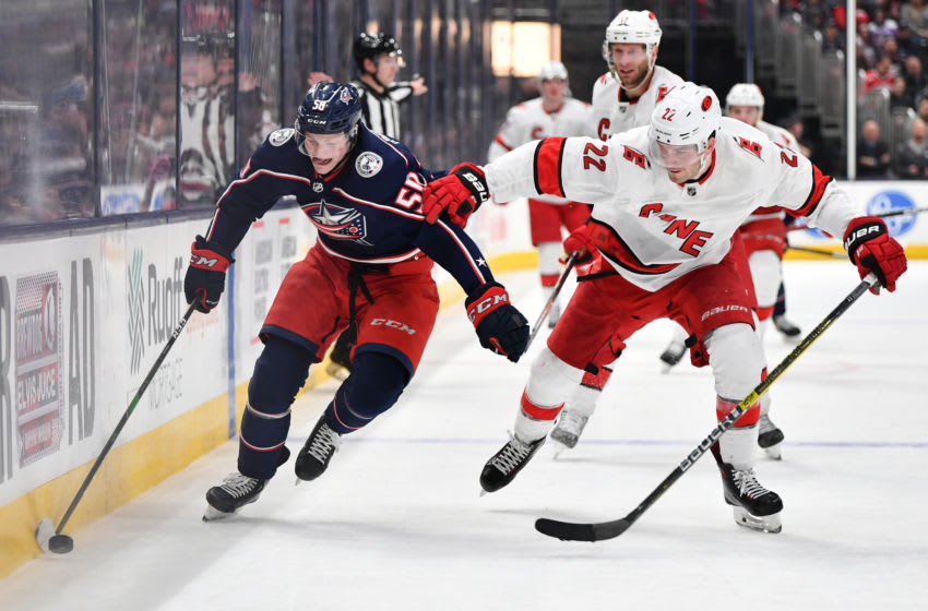 COLUMBUS, OH - JANUARY 16: Eric Robinson #50 of the Columbus Blue Jackets shields the puck from Brett Pesce #22 of the Carolina Hurricanes during the third period of a game on January 16, 2020 at Nationwide Arena in Columbus, Ohio. (Photo by Jamie Sabau/NHLI via Getty Images)