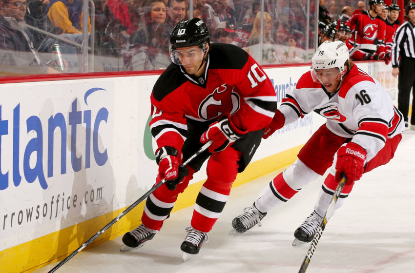 NEWARK, NJ - NOVEMBER 27: Peter Harrold #10 of the New Jersey Devils tries to keep the puck from Elias Lindholm #16 of the Carolina Hurricanes at Prudential Center on November 27, 2013 in Newark, New Jersey. (Photo by Elsa/Getty Images)