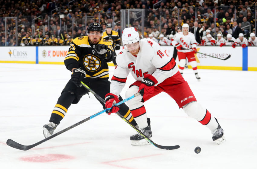 BOSTON, MASSACHUSETTS - DECEMBER 03: Brad Marchand #63 of the Boston Bruins and Dougie Hamilton #19 of the Carolina Hurricanes battle for control of the puck during the third period at TD Garden on December 03, 2019 in Boston, Massachusetts. The Bruins defeat the Hurricanes 2-0. (Photo by Maddie Meyer/Getty Images)