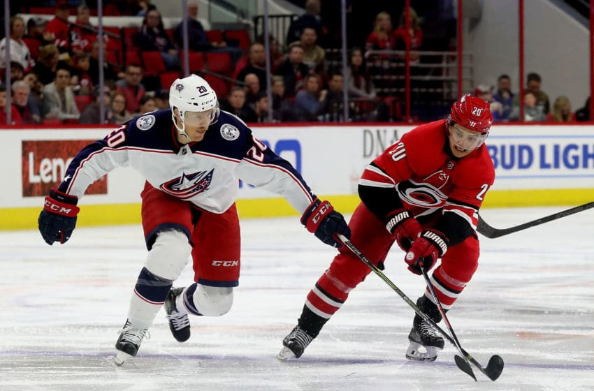 RALEIGH, NC - NOVEMBER 17: Sebastian Aho #20 of the Carolina Hurricanes and Riley Nash #20 of the Columbus Blue Jackets battle to control the puck during an NHL game on November 17, 2018 at PNC Arena in Raleigh, North Carolina. (Photo by Gregg Forwerck/NHLI via Getty Images)