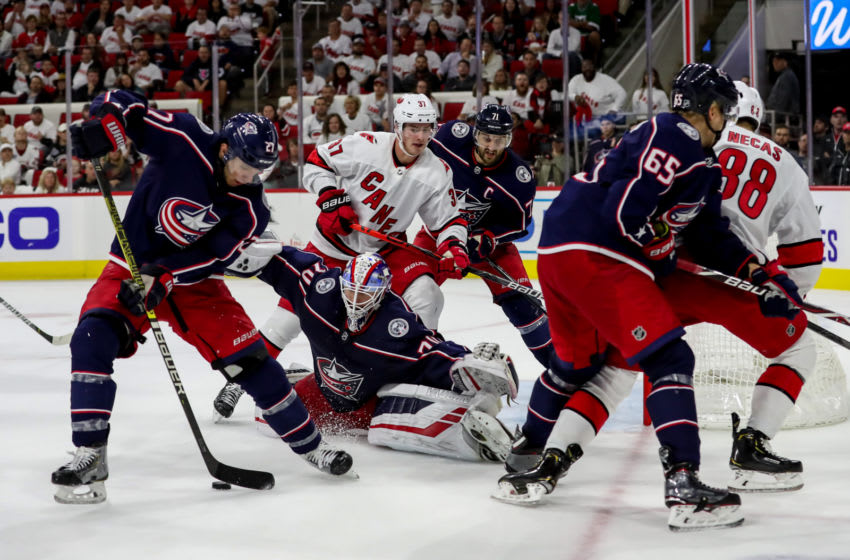 RALEIGH, NC - OCTOBER 12: Columbus Blue Jackets Goalie Joonas Korpisalo (70) spreads out to cover the net as Columbus Blue Jackets Defenceman Ryan Murray (27) gains control of the puck as a scramble takes place in front of the net during a game between the Columbus Blue Jackets and the Carolina Hurricanes on October 12, 2019 at the PNC Arena in Raleigh, NC. (Photo by John McCreary/Icon Sportswire via Getty Images)