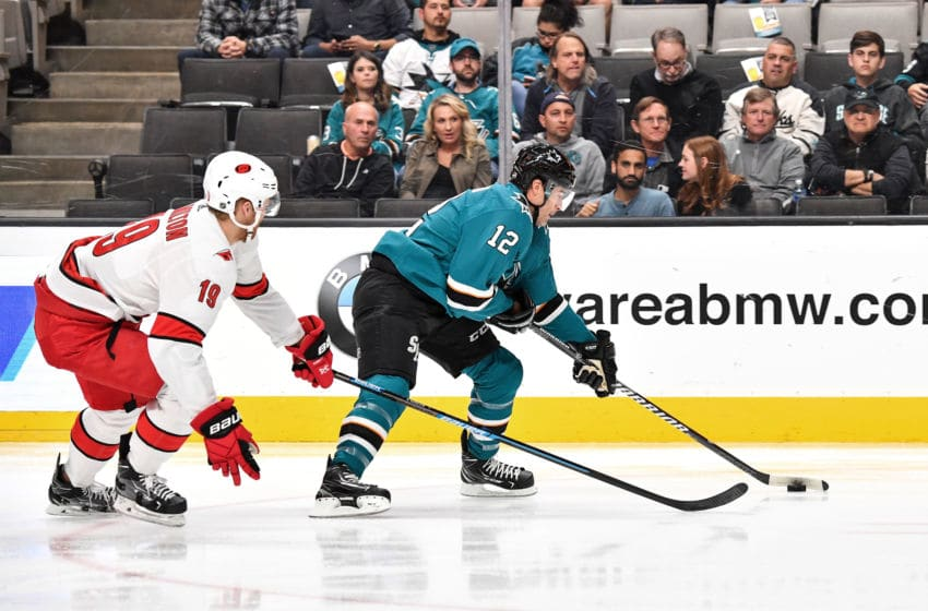 SAN JOSE, CA - OCTOBER 16: Patrick Marleau #12 of the San Jose Sharks skates ahead with the puck against Dougie Hamilton #19 of the Carolina Hurricanes at SAP Center on October 16, 2019 in San Jose, California. (Photo by Brandon Magnus/NHLI via Getty Images)