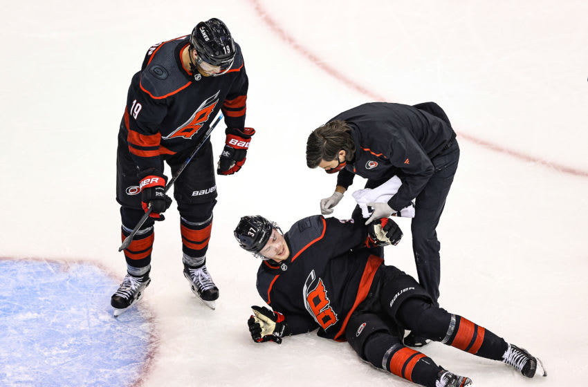 TORONTO, ONTARIO - AUGUST 15: Andrei Svechnikov #37 of the Carolina Hurricanes is tended to by the trainer after sustaining a knee injury against the Boston Bruins during the third period in Game Three of the Eastern Conference First Round during the 2020 NHL Stanley Cup Playoffs at Scotiabank Arena on August 15, 2020 in Toronto, Ontario. (Photo by Elsa/Getty Images)