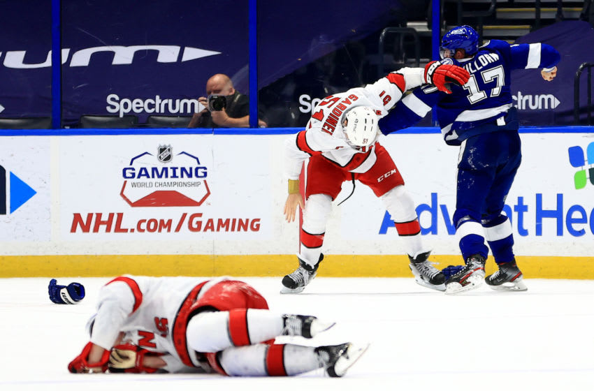 TAMPA, FLORIDA - APRIL 19: Alex Killorn #17 of the Tampa Bay Lightning and Jake Gardiner #51 of the Carolina Hurricanes fight during a game at Amalie Arena on April 19, 2021 in Tampa, Florida. (Photo by Mike Ehrmann/Getty Images)