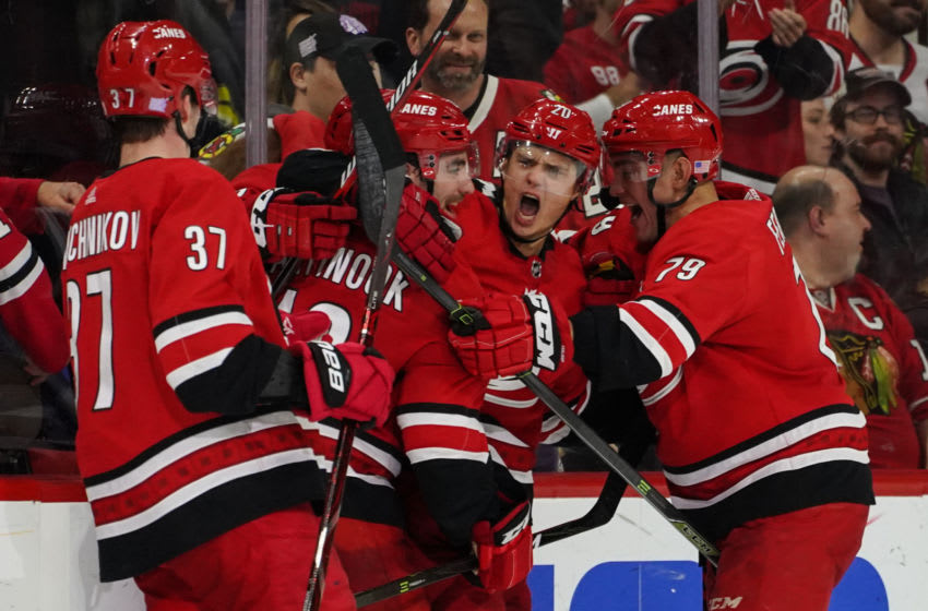 RALEIGH, NC - NOVEMBER 12: Carolina Hurricanes teammates Carolina Hurricanes Right Wing Andrei Svechnikov (37), Carolina Hurricanes Left Wing Jordan Martinook (48), Carolina Hurricanes Left Wing Micheal Ferland (79) mob Carolina Hurricanes Center Sebastian Aho (20) after scoring the game winning goal in overtime during a game between the Chicago Blackhawks and the Carolina Hurricanes at the PNC Arena in Raleigh, NC on November 12, 2018. (Photo by Greg Thompson/Icon Sportswire via Getty Images)