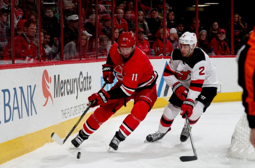 RALEIGH, NC - MARCH 2: Jordan Staal #11 of the Carolina Hurricanes plays a loose puck behind the net and controls it away from John Moore #2 of the New Jersey Devils during an NHL game on March 2, 2018 at PNC Arena in Raleigh, North Carolina. (Photo by Gregg Forwerck/NHLI via Getty Images)
