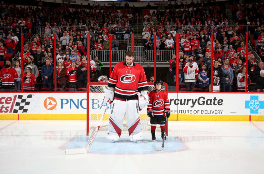 RALEIGH, NC - FEBRUARY 16: Cam Ward #30 of the Carolina Hurricanes reflects during the National Anthem as he shares the crease with his son Nolan Ward who is named starter of the game prior to an NHL game against the New York Islanders on February 16, 2018 at PNC Arena in Raleigh, North Carolina. (Photo by Gregg Forwerck/NHLI via Getty Images)
