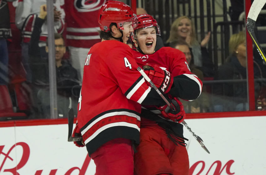 Mar 26, 2018; Raleigh, NC, USA; Carolina Hurricanes forward Warren Foegele (37) celebrates with defensemen Hayden Fleury (4) after scoring a goal during the first period against the Ottawa Senators at PNC Arena. Mandatory Credit: James Guillory-USA TODAY Sports
