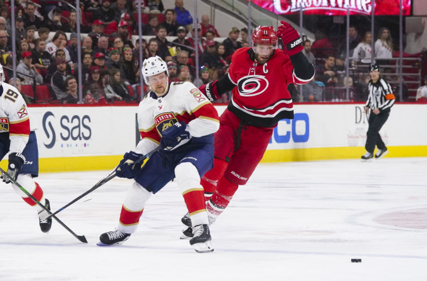 Dec 21, 2019; Raleigh, North Carolina, USA; Carolina Hurricanes center Jordan Staal (11) tries to slip the puck past the defense of Florida Panthers defenseman Anton Stralman (6) during the second period at PNC Arena. Mandatory Credit: James Guillory-USA TODAY Sports