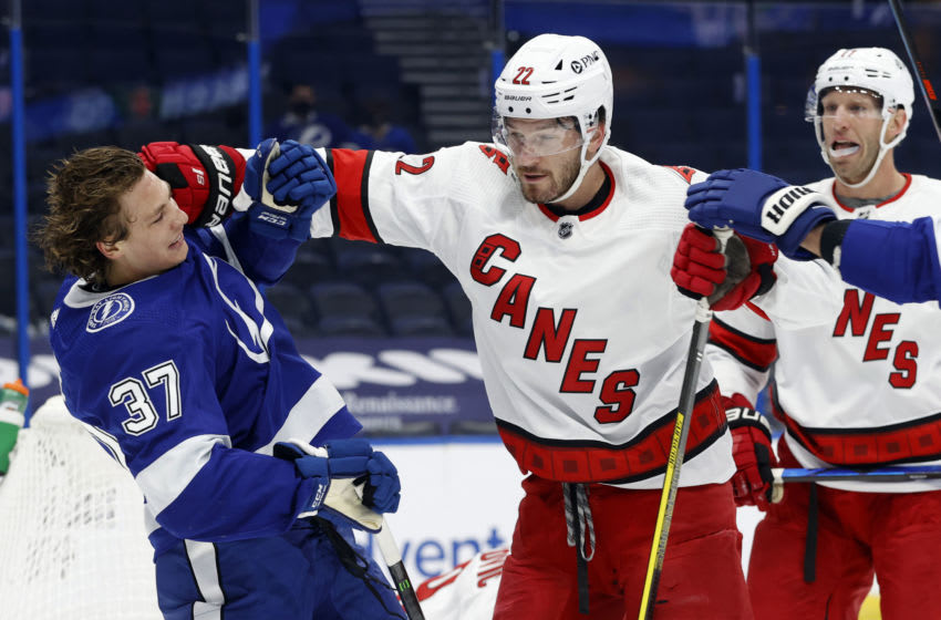 Feb 24, 2021; Tampa, Florida, USA; Carolina Hurricanes defenseman Brett Pesce (22) and Tampa Bay Lightning center Yanni Gourde (37) push each other during the first period at Amalie Arena. Mandatory Credit: Kim Klement-USA TODAY Sports