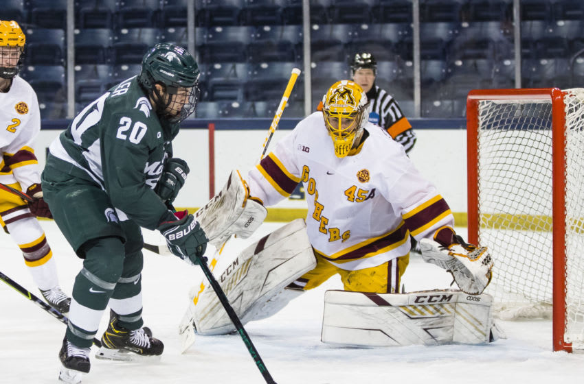 Mar 14, 2021; South Bend, Indiana, USA; Michigan State's Josh Nodler (20) shoots at Minnesota's Jack LaFontaine (45) at the Compton Family Ice Arena. Mandatory Credit: Michael Caterina/South Bend Tribune-USA TODAY NETWORK