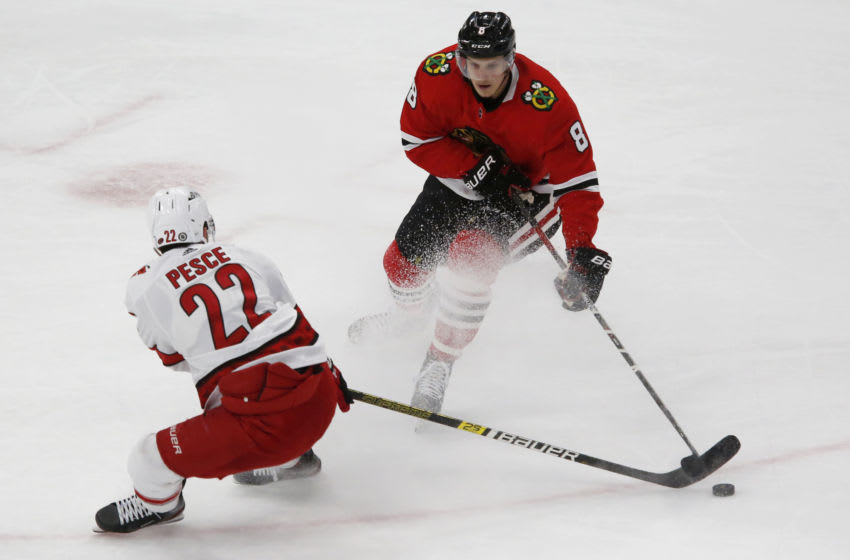 Mar 30, 2021; Chicago, Illinois, USA; Chicago Blackhawks Dominik Kubalik (8) and Carolina Hurricanes Brett Pesce (22) battle for the puck during the first period at United Center. Mandatory Credit: Eileen T. Meslar-USA TODAY Sports