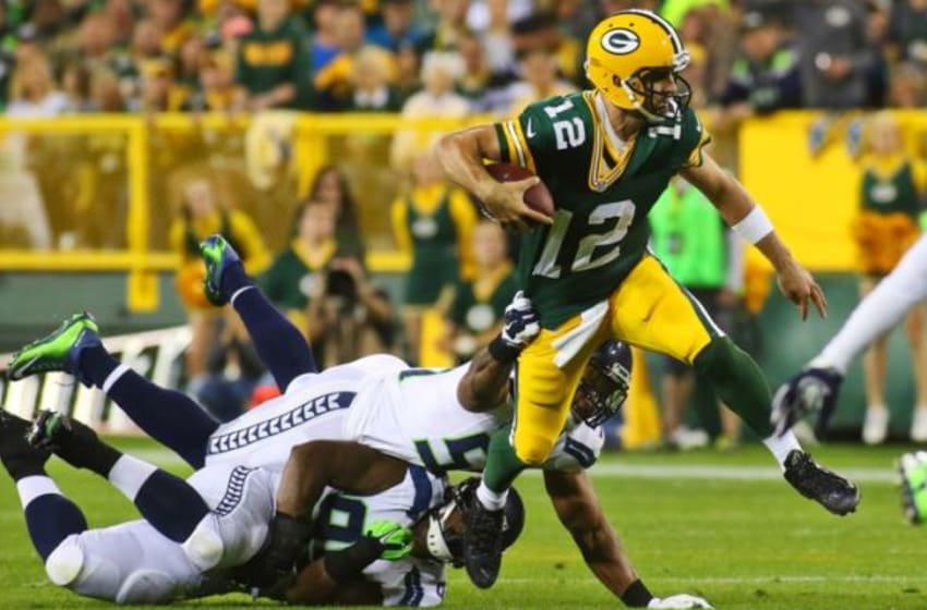 Sep 20, 2015; Green Bay, WI, USA; Green Bay Packers quarterback Aaron Rodgers (12) is tackled by Seattle Seahawks middle linebacker Bobby Wagner (54) during the first quarter at Lambeau Field. Mandatory Credit: Ray Carlin-USA TODAY Sports