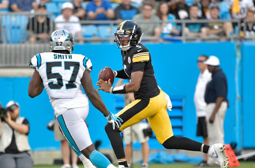 CHARLOTTE, NORTH CAROLINA - AUGUST 29: Joshua Dobbs #5 of the Pittsburgh Steelers rolls out under pressuer from Andre Smith #57 of the Carolina Panthers during their preseason game at Bank of America Stadium on August 29, 2019 in Charlotte, North Carolina. (Photo by Grant Halverson/Getty Images)