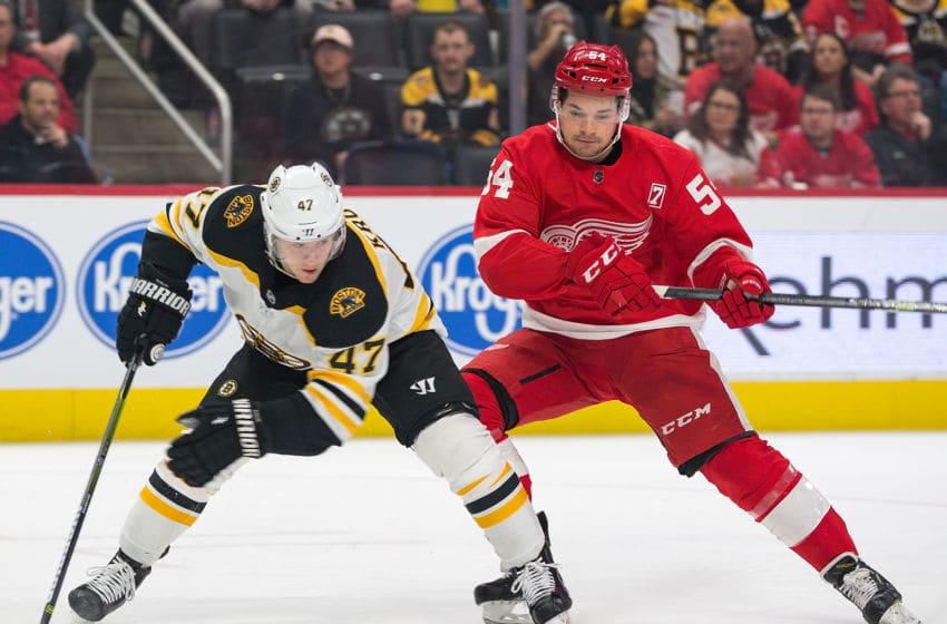 DETROIT, MI - MARCH 31: Torey Krug #47 of the Boston Bruins battles for the puck with Matt Puempel #54 of the Detroit Red Wings during an NHL game at Little Caesars Arena on March 31, 2019 in Detroit, Michigan. (Photo by Dave Reginek/NHLI via Getty Images)
