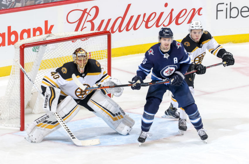 WINNIPEG, MB - MARCH 14: Mark Scheifele #55 of the Winnipeg Jets stands between goaltender Tuukka Rask #40 and Charlie McAvoy #73 of the Boston Bruins as they keep an eye on the play during third period action at the Bell MTS Place on March 14, 2019 in Winnipeg, Manitoba, Canada. The Jets defeated the Bruins 4-3. (Photo by Jonathan Kozub/NHLI via Getty Images)